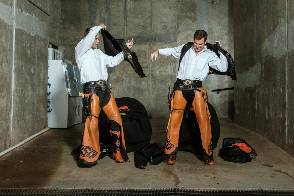 Austin Johnson, left, and Taylor Collins get dressed as Oklahoma State Cowboy's mascot Pistol Pete