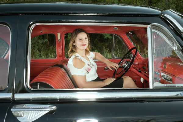 A portrait of Kim shot looking through the passenger window of her 1952 Ford Customline.