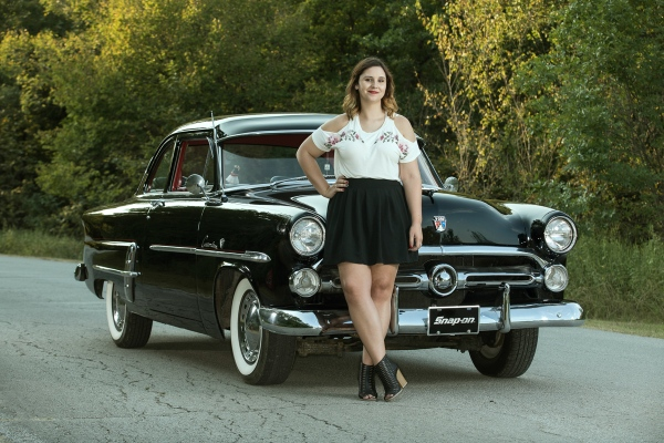 Portrait of Kim posing at the front of her black 1952 Ford Customline.