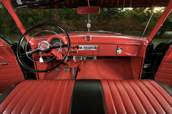 A view from the backseat of the bright red and black leather interior of the 1952 Ford Customline.