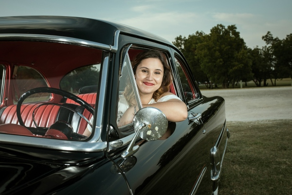 Picture of Kim leaning out of the driver's side window of her 1952 Ford Customline.